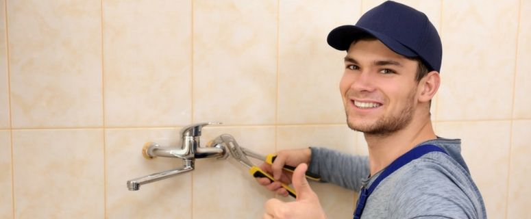 Plumber fixing a leak with a wrench and giving a thumbs up