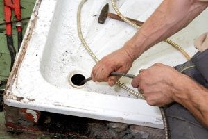 A plumber using a drain snake