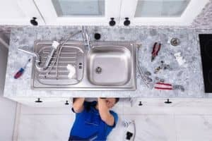 Plumber fixing kitchen plumbing