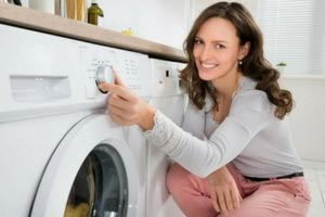 Woman turning on washing machine